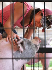 Jeanie Smith pets a pig during 2015 the Bellville Street Fair.