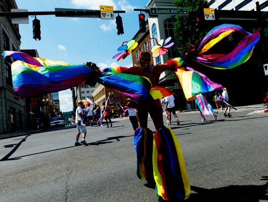 A person in stilts walks down Gay Street during the