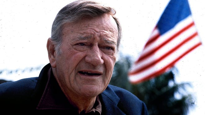 """John Wayne in 1978. Wearing a brown plaid coat worn by Wayne in 1945's """"Flame of Barbary Coast,"""" Republican Lt. Gov. Dan Patrick has declared a day in honor of the quintessential screen cowboy as he presided over the Senate Tuesday, May 26, 2015. He declared it John Wayne Day in Texas to mark the Hollywood legend's 108th birthday and named the actor an honorary Texan."""