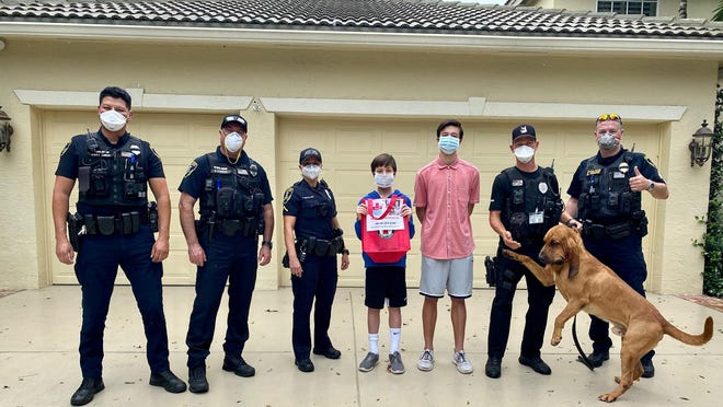 Gavin (middle) and Max (third from right) Gelinas stand next to Jupiter Police Department officers. The two brothers donated 100 meals to JPD.
