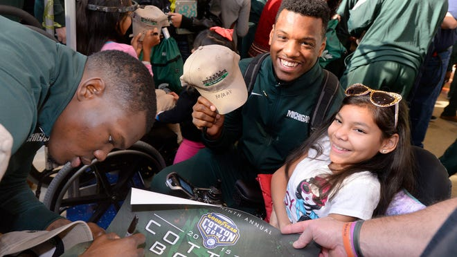 MSU defensive end Shilique Calhoun shows his hat signed by patient Yolany Briones, 11, at the Texas Scottish Rite Hospital for Children in Dallas, Texas.