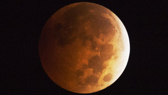A blood moon seen in Los Angeles in 2014. This weekend's hunter's supermoon will also have a red-orange hue.