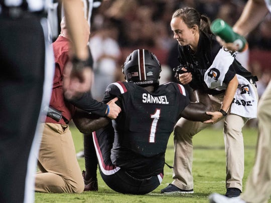 South Carolina wide receiver Deebo Samuel (1) is helped