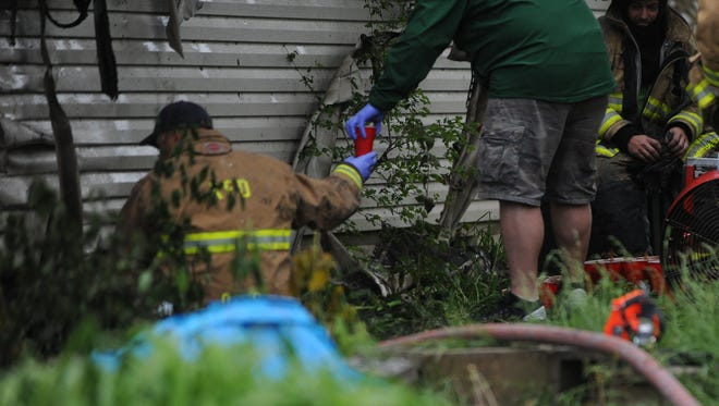 Plastic cups containing marijuana plants are passed out of the crawl space of a Williamsburg home Monday morning.
