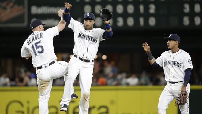 Seattle Mariners' Kyle Seager (15), Robinson Cano and Ketel Marte share congratulations after the team beat the Baltimore Orioles in a baseball game Thursday, June 30, 2016, in Seattle. The Mariners won 5-3. (AP Photo/Elaine Thompson)