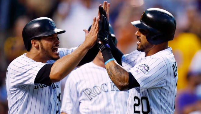 Colorado Rockies' Ian Desmond, right, celebrates as he crosses home plate with Nolan Arenado after Desmond hit a three-run home run off San Francisco Giants starting pitcher Jeff Samardzija on June 16.