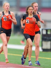 Northville freshman Yasmine Mansi (2) wins the 3,200 with teammates Olivia Harp (4) and Ana Barrott (right) second and third, respectively.