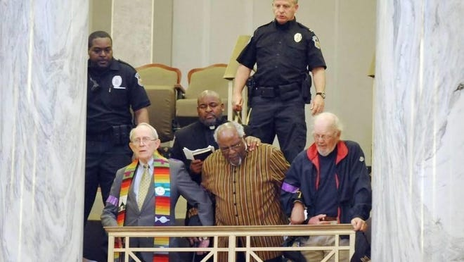 On May 6, 2014, Capitol police officers removed the Rev. John Bennett (left), the Rev. Wallace Hartsfield Sr. and the Rev. Sam Mann, who locked arms during a protest over the Missouri Senate's rejection of efforts to expand Medicaid coverage.