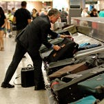 A traveler reaches for his luggage at Dulles International Airport on Aug. 30, 2011.
