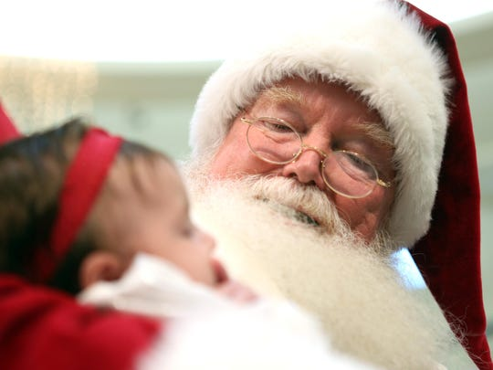 """Santa gazes down upon a peaceful Lilliana Sarro, 2.5 months old, of Toms River. The Santa Claus at the Ocean County Mall has been there for about a decade. We will discuss with """"Santa"""" why he keeps coming back to Ocean County year after year, how the children have changed, what are the strangest requests he has received from children, do some kids really lose control of their bladder as the immortalized in the movie classic """"A Christmas Story,"""" and what does Santa do to prevent children from pulling on his whiskers. Toms River, New Jersey. Saturday, January 24, 2015. David Gard /Correspondent"""