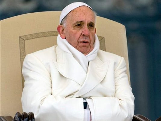 FILE - In this Wednesday, Nov. 27, 2013 file photo Pope Francis tries to keep himself warm as he attends his weekly general audience in St. Peter's Square at the Vatican. Pope Francis released his much-anticipated encyclical 'Laudato Si' (Praise Be), on the environment Thursday, declaring an urgent need for the political and spiritual conversion of global leaders and individuals to dedicate themselves to curbing climate change and ending policies and personal habits that destroy creation.