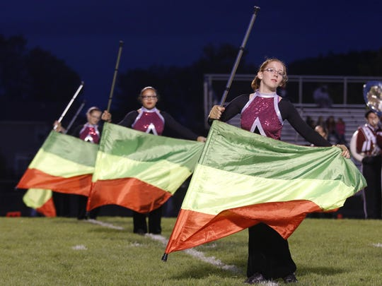 The Okemos marching band and flag corps performs Friday, Sept. 11, 2015, in Okemos, Mich.