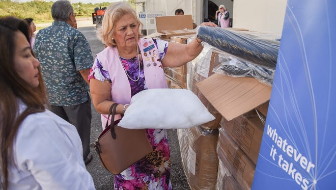 Members of the Guam Memorial Hospital Volunteers Association receive a donation of 500 blankets, 1,350 pillows, and 600 pillowcases from United Airlines at the United's warehouse in Tiyan on Dec. 9, 2016.