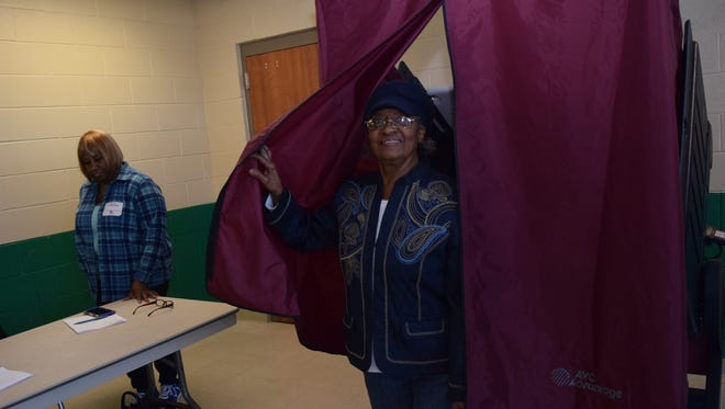 Vera M. Bonton comes out of a voting booth after voting in a presidential preference primary at a precinct at Peabody Magnet High School on Saturday. At left is poll commissioner Joanette Anderson.