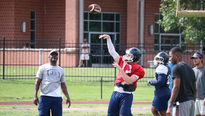 Jackson State assistant coach Sleepy Robinson (left) looks on as freshman quarterback Jack Strouse tosses the ball during practice on Monday, August 6 in Jackson.