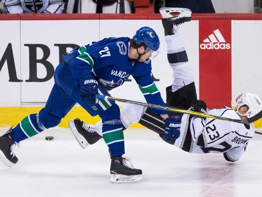 Vancouver Canucks' Ben Hutton, left, checks Los Angeles Kings' Dustin Brown during the second period of an NHL hockey game Saturday, Dec. 30, 2017, in Vancouver, British Columbia. (Darryl Dyck/The Canadian Press via AP)