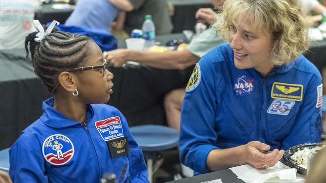 FILE - NASA astronaut Dottie Metcalf-Lindenburger talks with Space Camp camper Bria Jackson of Atlanta before giving a speech at the U.S. Space & Rocket Center in Huntsville, Ala. in this July 13, 2018, file photo. Space Camp, an educational program attended by nearly 1 million people, said Tuesday, July 28, 2020, it's in danger of closing without a cash infusion because of the coronavirus pandemic.