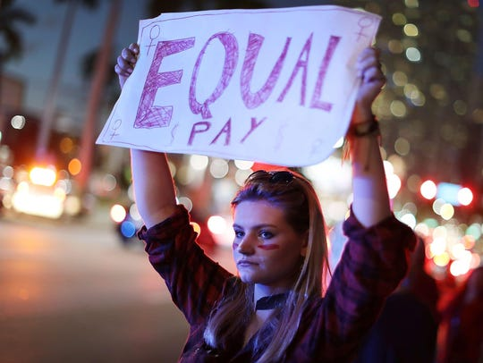 A demonstrator holds a sign reading, 'Equal Pay,' as