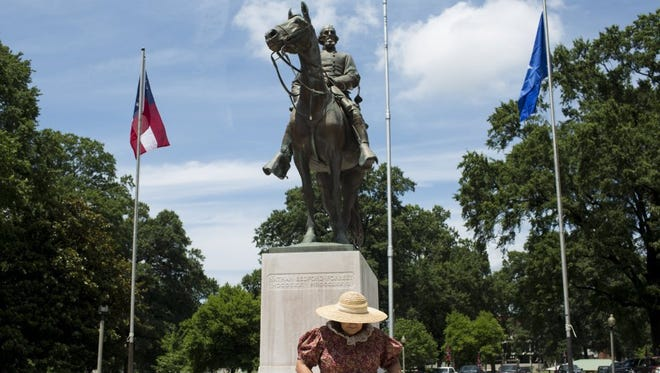"""Janie McDonald walks away from the Nathan Bedford Forrest statue after getting her picture taken during a Confederate-themed rally July 10, 2016, at Health Sciences Park to celebrate the birthday of Forrest. """"We just love history,"""" said McDonald, who is the great-great-granddaughter of John Riley, who rode with Forrest. McDonald is a member of the United Daughters of the Confederacy Varina Howell Davis 2559 group."""