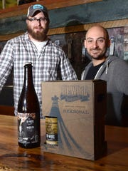 Hi-Wire Brewing co-owners Chris Frosaker, left, and Adam Charnack stand with their seasonal coffee milk stout, in the box, and a 2013 collaborative beer made with Burial Beer Co.
