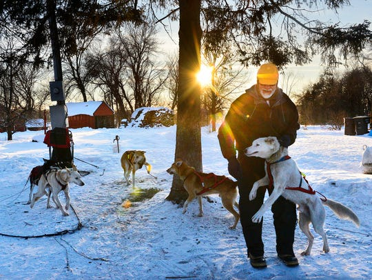 Melrose area musher Linus Meyer moves one of the dogs