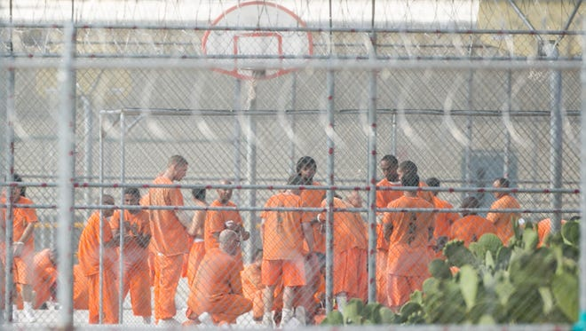 Prison inmates are seen on the yard through the fence at Arizona State Prison-Kingman in Golden Valley, AZ on July 4, 2015.