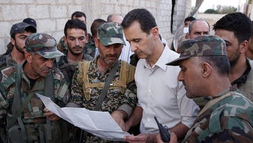 Syrian President Bashar al-Assad, shown in a file photo provided by the Syrian Arab news agency in June 2016, is  shown R) meeting on June 26, 2016, with Syrian soldiers in  Marj al-Sultan airport in Eastern Ghouta of the Damascus countryside.