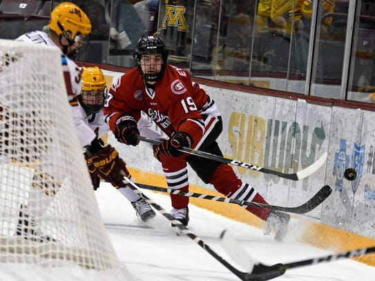 St. Cloud State's Mikey Eyssimont works a puck behind the boards during a game at 3M Arena at Mariucci in Minneapolis on Jan. 7, 2018.