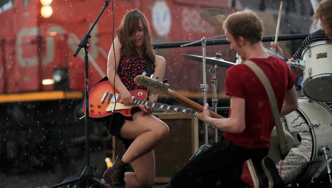 Holly Trasti of Holly and the Nice Lions plays guitar as it begins to rain during the band's performance at the igNight Market on Saturday in downtown Green Bay.