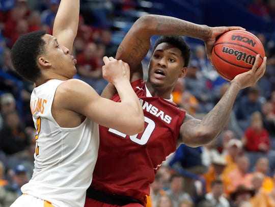Arkansas' Darious Hall, right, looks to pass as Tennessee's