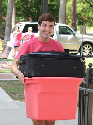 Ryan Studer, an upperclassman at Lander University, works with other volunteers to help incoming freshmen by carrying heavy items to their residence halls during Freshman Move-In Day.