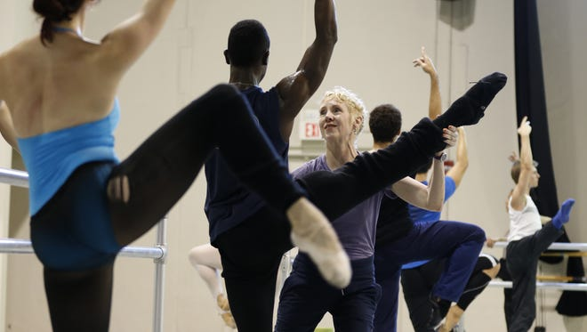 Victoria Morgan, Artistic Director and CEO, Cincinnati Ballet, center, works with corps de ballet dancer Joshua Bodden as she teaches a class to dancers.