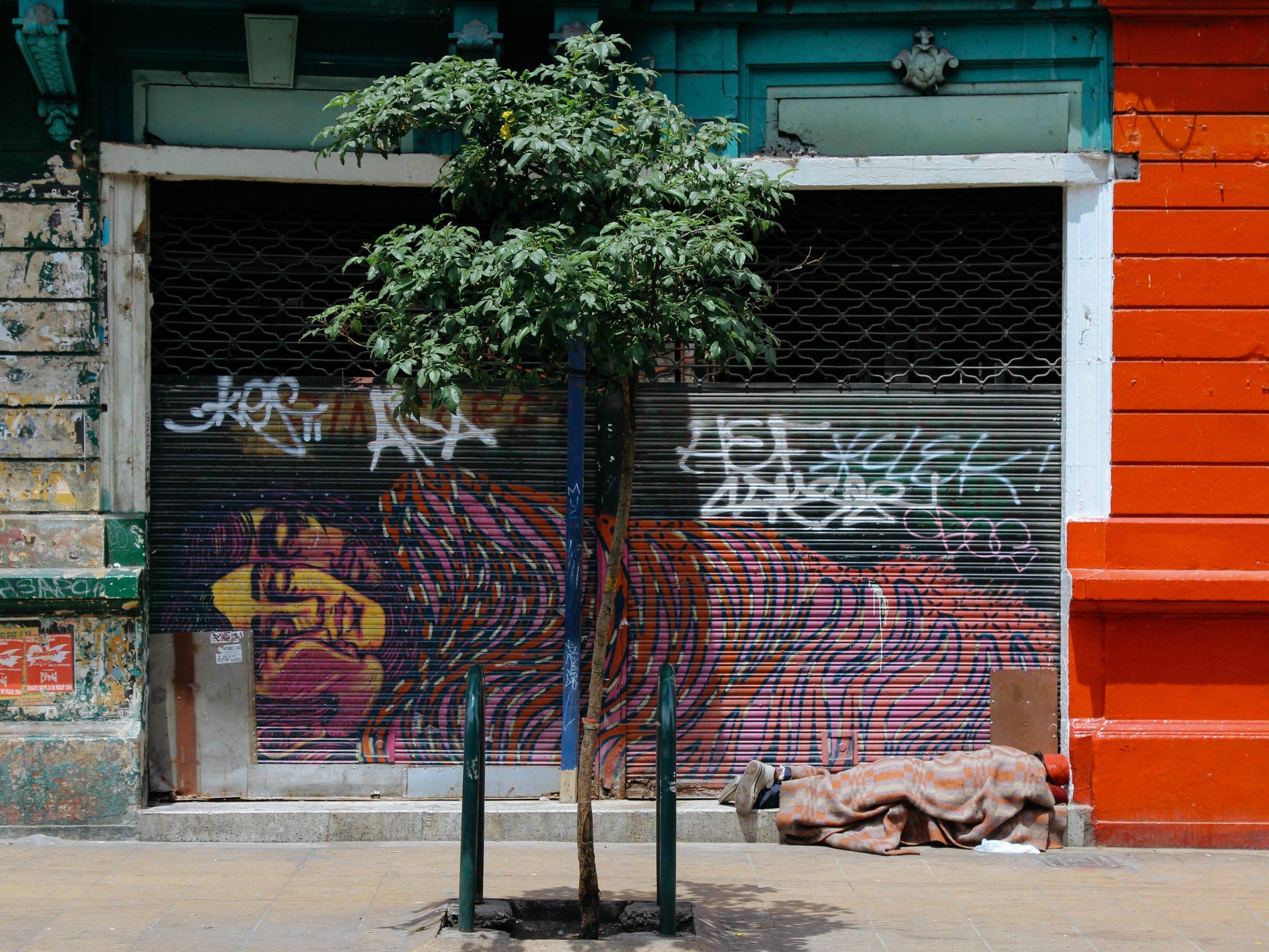 A man sleeps beneath a Bastardilla piece along Bogotá's