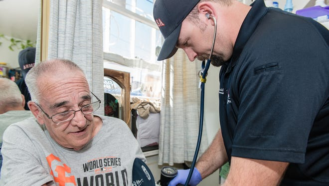 Paramedic Ryan Ramsdell checks 68-year-old Earl Mayes blood pressure during a home visit on March 26, 2015 in Sparks, Nevada. Ramsdell is part of a community health plan to help reduce avoidable emergency room visits by treating patients at home