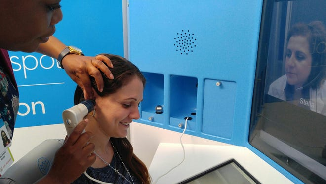 Jessica Christianson uses a telemedicine kiosk at the Palm Beach County School District's administrative building in West Palm Beach, Fla. A medical device called an otoscope connected to the kiosk lets nurse practitioner Stella Leviyeva in Miami examine the inside of Christianson's ear.