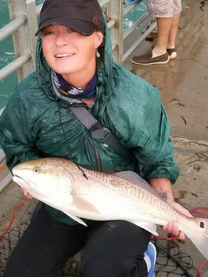 Desiree Vaughn, of Sebastian, caught this redfish in the rain Tuesday at Sebastian Inlet's North Jetty and posted her photo on the Sebastian Fishing Club Facebook page.