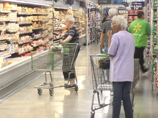 Wal-Mart Neighborhood Market shoppers browse the aisles of the new store after its grand opening Wednesday morning.