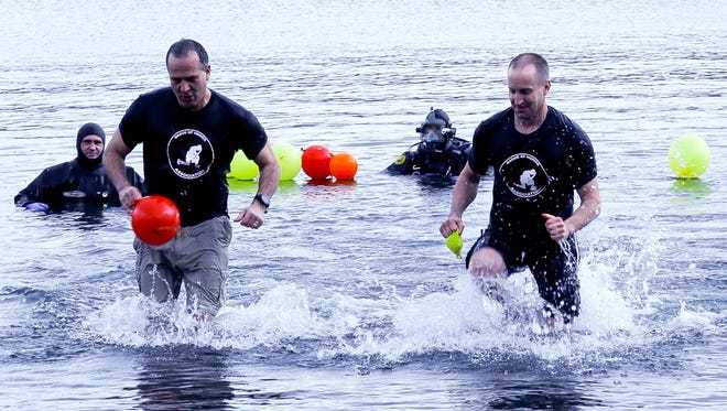 Ithaca Police Chief John Barber, right, rushes out of Cayuga Lake on a 29-degree day after participating in the first Ithaca Chill Challenge. Organized by Ithaca Community Recovery, more than $20,000 was raised.