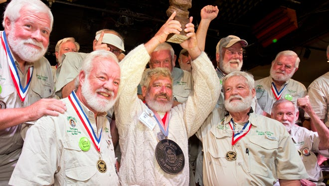 """In this  Saturday, July 23, 2016, photo provided by the Florida Keys News Bureau,  Dave Hemingway, center, hoists his trophy after winning the 2016 Ernest """"Papa""""  Hemingway Look-Alike Contest at Sloppy Joe's Bar in Key West, Fla. Success for Dave Hemingway came on the Macon, N.C., resident's seventh attempt to win the coveted title at the highlight event of the island city's annual Hemingway Days festival that ends Sunday. Dave Hemingway is not related to Ernest Hemingway who lived and wrote in Key West in the 1930s."""