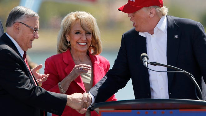 Maricopa County Sheriff Joe Arpaio, left, and former Arizona governor Jan Brewer, center, greet Republican presidential candidate Donald Trump at a rally at Fountain Park in Fountain Hills, Ariz., on Saturday, March 19, 2016. Trump announced a campaign rally in Arizona for next week. (Allen J. Schaben/ Los Angeles Times/TNS)