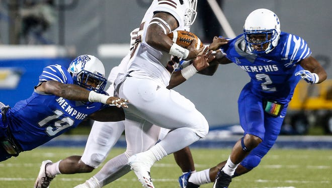 "University of Louisiana-Monroe running back Kayin White (middle) is tackled by the University of Memphis defenders Shaun Rupert (left) and Terrell ""TJ"" Carter (right) during third quarter action at the Liberty Bowl Memorial Stadium."