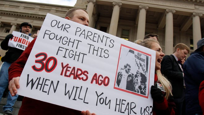 """From left, John Leep, Rowan County High School Teacher and his sister, Jessica Page, a Campbellsburg Elementary teacher listen to a speaker during """"The People's Movement- United We Stand Rally"""" held on the Capitol steps in Frankfort, Monday, March 12."""