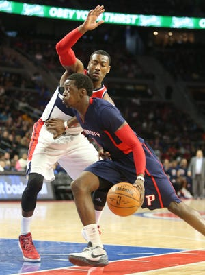 Pistons guard Reggie Jackson drives against  Washington Wizards guard John Wall at the Palace of Auburn Hills.