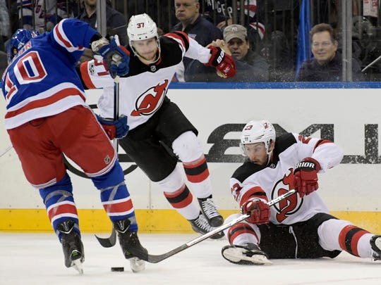 New Jersey Devils right wing Stefan Noesen (23) attempts to get his stick on the puck as New York Rangers left wing J.T. Miller (10) and Devils center Pavel Zacha (37) close in during the first period of an NHL hockey game Saturday, Dec. 9, 2017, at Madison Square Garden in New York.