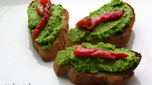 Pea Pesto Bruschetta is topped with roasted red peppers for a tasty appetizer