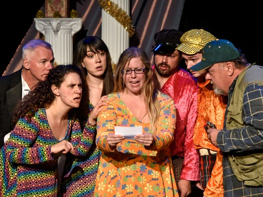 Cast members gather in a scene during a rehearsal for
