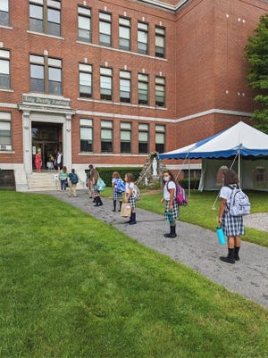 Observing social distancing guidelines, sanitizing hands and wearing masks, students at Holy Family Academy returned to class on Tuesday, Sept. 8.