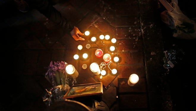 People light candles Nov. 27, 2016, a vigil at Bourbon and Iberville streets for Demontris Toliver, killed in a shooting in the early morning in the French Quarter section of New Orleans.