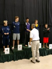 Lakeview's Levi Youmans is awarded  his state championship medal by Spartan swim coach Willie English.