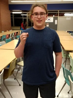 Sam Sweetman holds up his medal after his fifth-place finish at the Fond du Lac High School Math Team's first meet of the season.